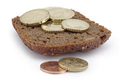 Heap of coins on a slice of bread. A white background stock photos