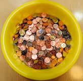 Heap of coins in yellow bowl Stock Photos