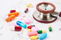 Heap of color pills and tablets with stethoscope medical. Heap of color pills and tablets with stethoscope medical on chemical formulas background stock photos