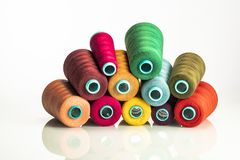 Heap colored industrial spools arranged on white background royalty free stock images