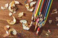 Heap of colored pencils with shavings on the wooden background. Top view Stock Photography