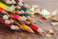 Heap of colored pencils with shavings, wooden background, top view. Heap of colored pencils with shavings on the wooden background, top view Stock Photography