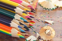Heap of colored pencils with shavings, wooden background, top view. Heap of colored pencils with shavings on the wooden background, top view Stock Photos