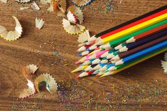 Heap of colored pencils with shavings, wooden background, top view. Heap of colored pencils with shavings on the wooden background, top view Stock Images