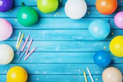 Heap of colorful balloons, confetti and candles on turquoise vintage table top view. Birthday party background. Greeting card.
