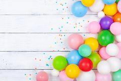Heap of colorful balloons and confetti on white table top view. Festive or party background. Flat lay. Birthday greeting card. Heap of colorful balloons and stock photo
