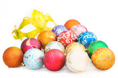 Heap of colorful christmas baubles and carnival mask on white ba Stock Photography
