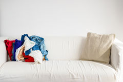 Heap of colorful clothing on sofa Royalty Free Stock Photos
