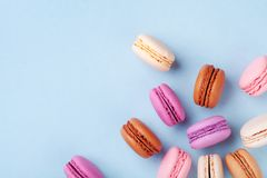 Heap of colorful dessert macaron or macaroon on blue background top view. Flat lay stock photos