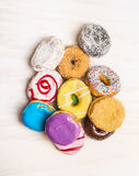 Heap of colorful donuts on white wooden background, top view. Heap of colorful donuts white wooden background, top view stock image