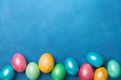 Heap of colorful eggs on blue table top view. Holiday Easter banner. Copy space for text. royalty free stock image