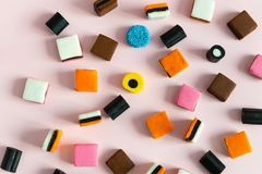 Heap of colorful Liquorice allsorts on pink background. Sweets royalty free stock photo