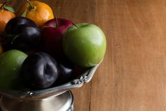 Heap colourful fruit in the silver bowl on the rustic wood table background. Red and green apple plums and tangerine in the silver bowl on the wood table royalty free stock photo