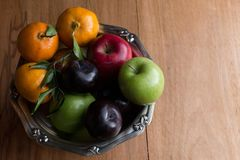 Heap colourful fruit in the silver bowl on the rustic wood table background. Red and green apple plums and tangerine in the silver bowl on the wood table stock image