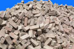 Heap of construction bricks. A heap of red-brown construction bricks against a blue background Stock Photography