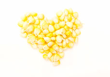 Heap of corn kernels in shape of a heart, on white Royalty Free Stock Photos