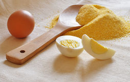 Heap of corn meal, wooden spoon and eggs Royalty Free Stock Image