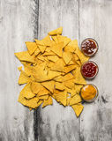 Heap of corn nachos chips with various dips on rustic wooden background, top view. Heap of corn nachos chips with various dips rustic wooden background, top view royalty free stock photography