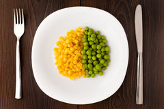 Heap of corn seeds and peas on plate Stock Photo