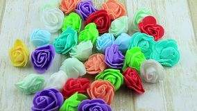 Heap of decorative flowers roses. Artificial multi-colored flowers on a wooden background stock video footage