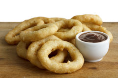 Heap of deep fried onion or calamari rings with barbecue dip on Stock Images