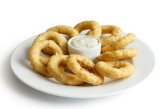Heap of deep fried onion or calamari rings with chilli dip on wh. Heap of deep fried onion or calamari rings with garlic mayonnaise dip on white plate Royalty Free Stock Photos