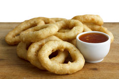 Heap of deep fried onion or calamari rings with chilli dip on wo Stock Photo