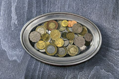 Heap of different coins. On a silver platter stock images