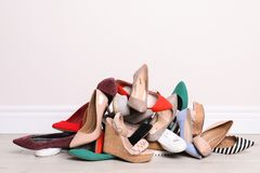 Heap of different shoes on floor. Against light wall royalty free stock photography