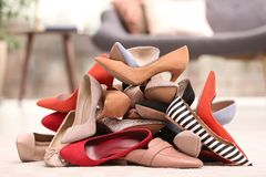 Heap of different shoes on floor. In room stock photos