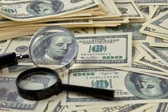 Heap of dollars and magnifiers. Concept close-up money dollars and magnifiers background Stock Photo