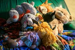 Heap of dolls and stuffed animals, on a green couch royalty free stock photo