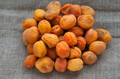Heap of dried apricots on hessian linen fabric Stock Images