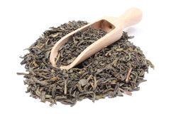 Heap of dried green tea on wooden spoon Stock Photo