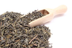 Heap of dried green tea on wooden spoon. White background Stock Photography