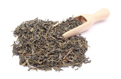 Heap of dried green tea on wooden spoon. White background Stock Photo