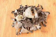 Heap of dried Horn of Plenty mushrooms on bamboo Royalty Free Stock Photos