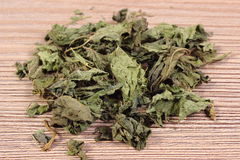 Heap of dried nettle on wooden surface Royalty Free Stock Photography