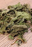 Heap of dried nettle on wooden surface Stock Photography