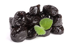 Heap of dried plums or prunes with a mint leaf isolated on white background Royalty Free Stock Image