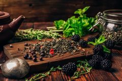 Green Tea with Blackberry, Mint and Thyme. Heap of Dry Green Tea and Fresh Blackberries on Wooden Cutting Board. Bundles of Mint and Thyme Leaves. Clay Kettle Stock Image