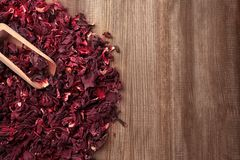 Heap of dry hibiscus tea with scoop on wooden background royalty free stock image
