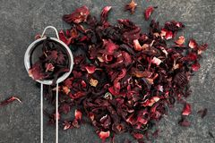 Heap of dry hibiscus tea with sieve on grey background stock image