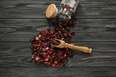 Heap of dry hibiscus tea with wooden scoop on table royalty free stock image