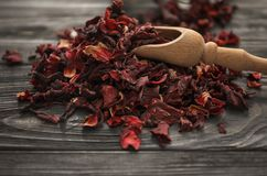 Heap of dry hibiscus tea with wooden scoop on table stock photography