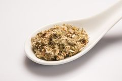 Heap of dry medical herbal tea in white ceramic spoon Royalty Free Stock Photo