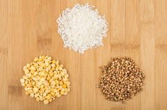 Heap of dry rice, buckwheat and peas on board Royalty Free Stock Photos