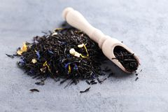 Heap of dry tea. With wooden scoop on grey table Royalty Free Stock Photography