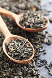 Heap of dry tea. With wooden spoon on grey table Royalty Free Stock Photography