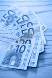 Heap of euro banknotes on a wooden table Royalty Free Stock Images